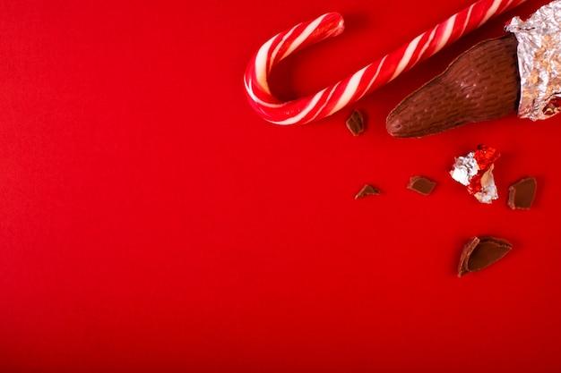 Bożenarodzeniowi tradycyjni cukierki na czerwonym tle. czekoladowe mikołajki z laską cukrową.