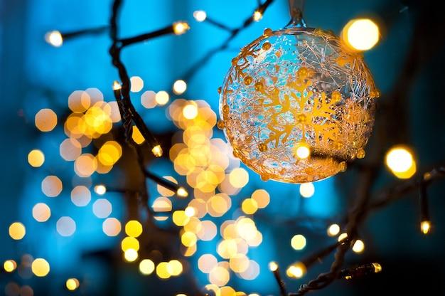 Bożenarodzeniowi złociści światła bożenarodzeniowej girlandy błękitny tło
