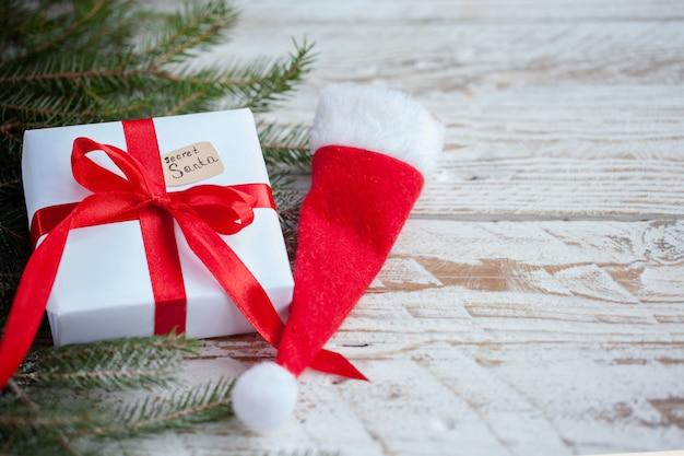 Bożenarodzeniowy biały pudełko lub teraźniejszość z czerwoną faborkiem dla tajnego santa z santa kapeluszem na drewnianym stole.