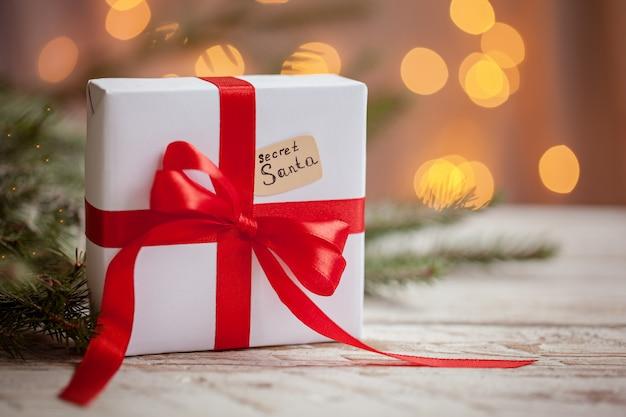 Bożenarodzeniowy biały pudełko lub teraźniejszość z czerwonym faborkiem dla tajnego santa na drewnianym stole.