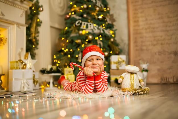 Bożenarodzeniowy chłopiec z czerwoną cukierek trzciną i santa kapeluszem