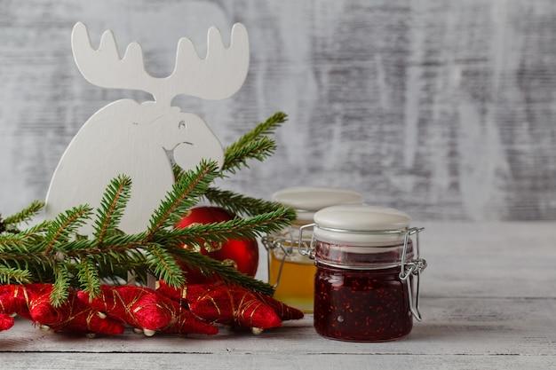 Bożenarodzeniowy dżemu słój z świąteczną dekoracją na białym drewnianym stole, selekcyjna ostrość. jadalny prezent