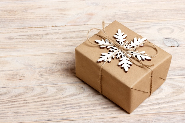 Bożenarodzeniowy handmade prezenta pudełko dekorujący z rzemiosło papierem i białym płatkiem śniegu na białego drewnianego tła odgórnym widoku. motyw świątecznych świąt zimowych. szczęśliwego nowego roku. wesołych świąt z życzeniami