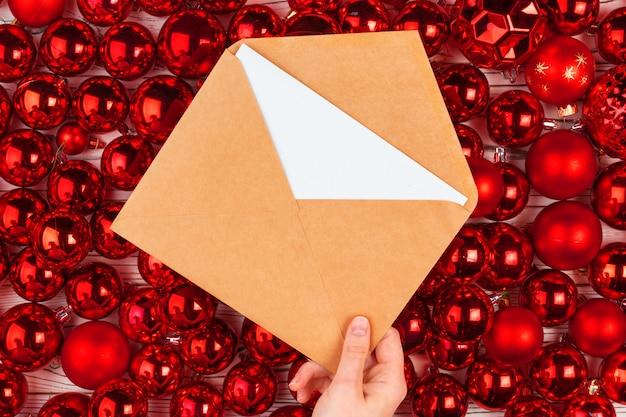 Bożenarodzeniowy kartka z pozdrowieniami lub list przeciw backround z czerwonymi baubles
