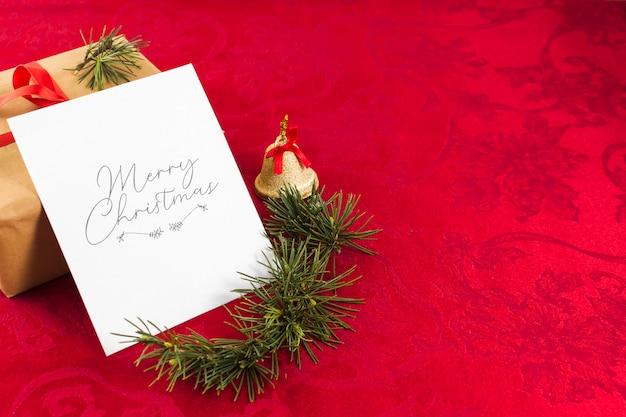 Bożenarodzeniowy kartka z pozdrowieniami na czerwień stole