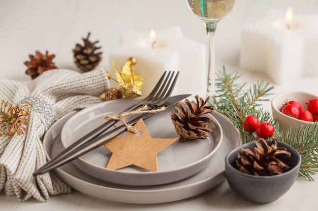 Bożenarodzeniowy piękny stołowy położenie z szampanem i świeczkami.