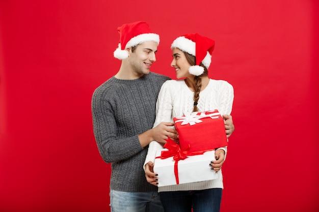 Bożenarodzeniowy pojęcie - przystojny młody chłopak w bożenarodzeniowym pulowerze zaskakuje jego dziewczyny z prezentami.
