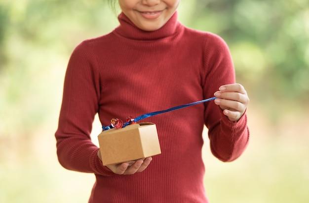 Bożenarodzeniowy portret szczęśliwy uśmiechający się małe dziecko dziewczynka z pudełkiem w pobliżu zielonej gałęzi drzewa. zielone liście bokeh z tła ostrości z lasu.
