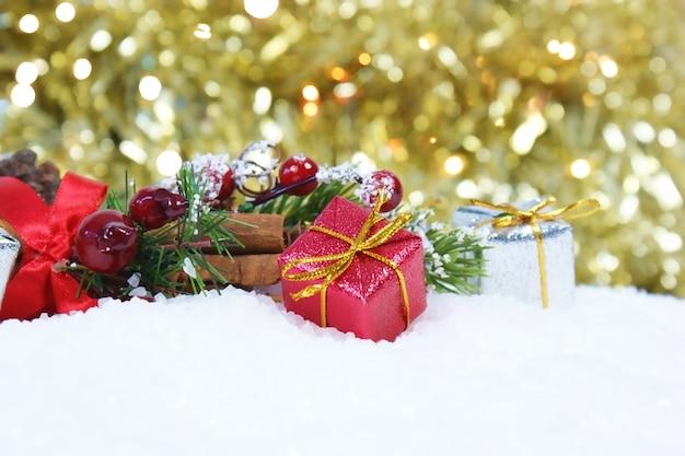 Bożenarodzeniowy prezent i dekoracje w śniegu przeciw złocistemu bokeh zaświeca tło