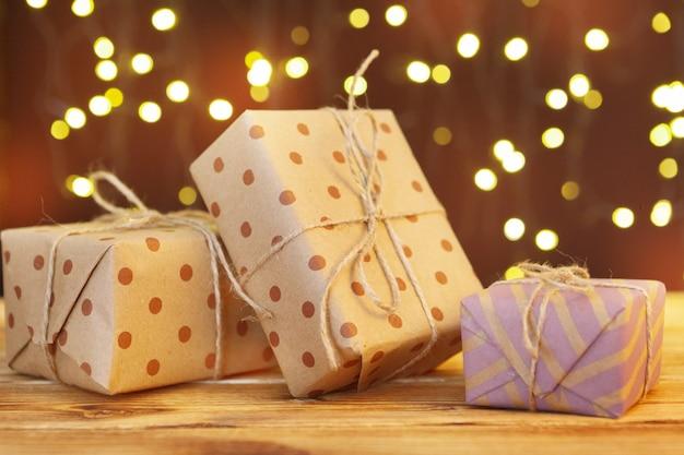 Bożenarodzeniowy prezenta pudełko na drewnianym stole przeciw brown bokeh
