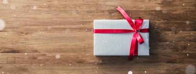Bożenarodzeniowy prezenta pudełko na drewno stołu sztandaru tle