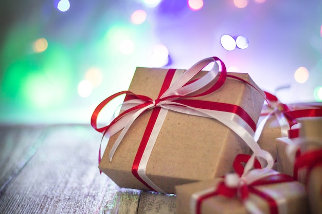 Bożenarodzeniowy prezenta pudełko przeciw bokeh tłu. karta z pozdrowieniami świątecznymi