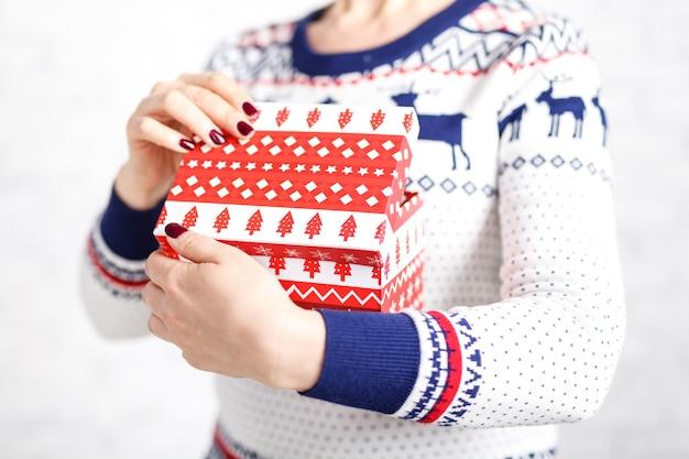 Bożenarodzeniowy prezenta pudełko w żeńskiej ręce na białym tle