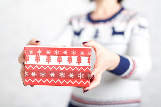 Bożenarodzeniowy prezenta pudełko w żeńskiej ręce na biel powierzchni