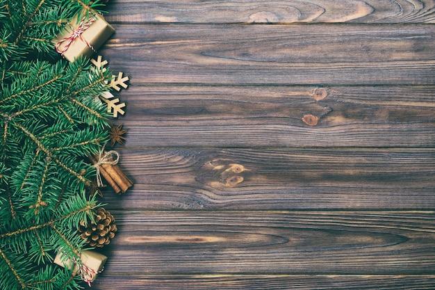 Bożenarodzeniowy rocznik, stonowany tło z jedlinowym drzewem i prezenta pudełko na drewnianym stole. widok z góry
