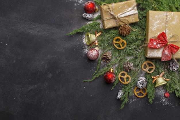Bożenarodzeniowy skład iglaste gałąź, dekoracje i cukierki na ciemnym tle. leżał płasko. widok z góry koncepcja natura nowy rok. skopiuj miejsce