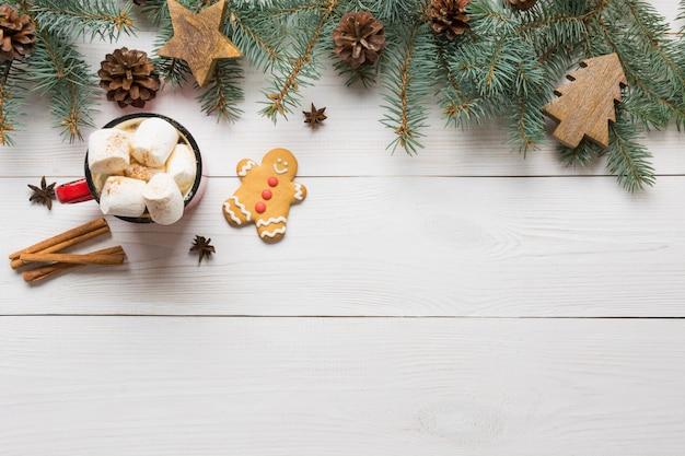 Bożenarodzeniowy skład kawa z marshmallow i jodłą rozgałęzia się na białej drewnianej desce