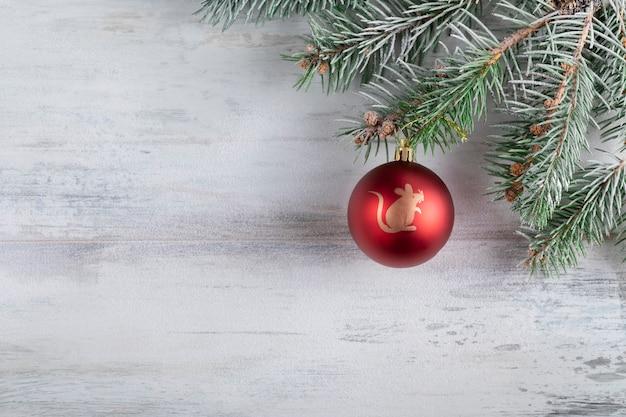 Bożenarodzeniowy skład na drewnianym zakrywającym w białym śniegu. dekorację świąteczną z czerwoną piłkę.