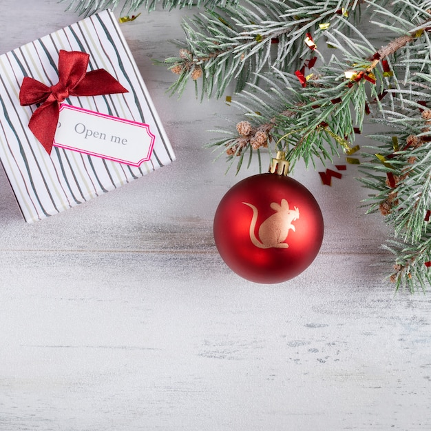 Bożenarodzeniowy skład na drewnianym zakrywającym w białym śniegu. pudełka na prezenty świąteczne z czerwonymi kokardkami, zaśnieżone gałęzie jodły, świąteczne ozdoby z czerwoną kulką.