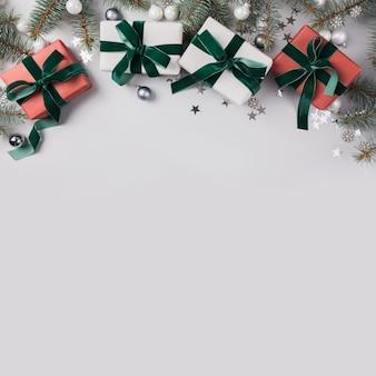 Bożenarodzeniowy skład z jodłą rozgałęzia się drzewa, czerwoni prezenty na świetle. karta świąteczna. zimowe wakacje. .