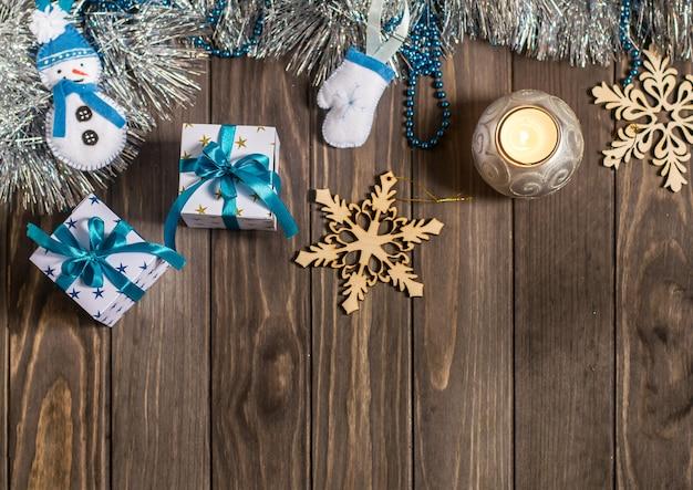 Bożenarodzeniowy skład z prezentami, świeczką, dekoracyjnymi płatkami śniegu i ręcznie robiony bożenarodzeniowymi filcowymi zabawkami na drewnianym tle