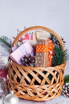 Bożenarodzeniowy skład z pudełkiem, koszem, sosnowymi rożkami i dekoracjami na biały drewnianym z copyspace