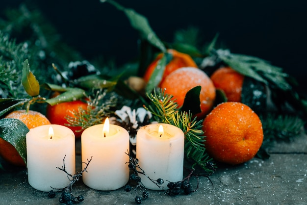 Bożenarodzeniowy skład z tangerines, sosnowymi rożkami, orzechami włoskimi i świeczkami na drewnianym tle.