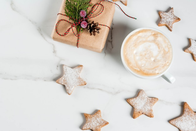 Bożenarodzeniowy śniadanie, kawowy kubek z piernikowymi gwiazdowymi ciastkami, z prezentem lub teraźniejszością, na białym drewnianym stołowym odgórnego widoku copyspace