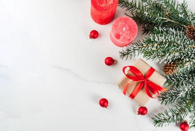 Bożenarodzeniowy tło dla kartka z pozdrowieniami. choinka rozgałęzia się z śnieżnym skutkiem z świąteczną czerwoną faborkiem, sosnowymi rożkami, prezentów pudełkami i świeczkami, na bielu marmuru tła odgórnym widoku