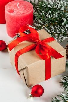 Bożenarodzeniowy tło dla kartka z pozdrowieniami. gałęzie choinkowe z efektem śniegu z świąteczną czerwoną wstążką, szyszki, pudełka i świece, na tle białego marmuru