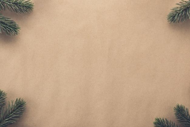 Bożenarodzeniowy tło granicy projekt z zieloną sosną przy kątami na brown papierze