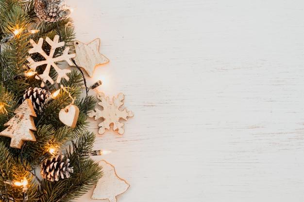 Bożenarodzeniowy tło - jodły liście i nieociosani elementy dekoruje na białym drewno stole. kreatywny układ płaski i widok z góry.