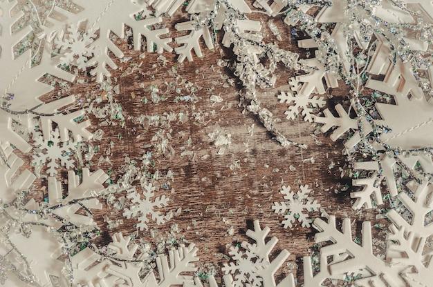 Bożenarodzeniowy tło z białymi płatkami śniegu na drewnianym stole.