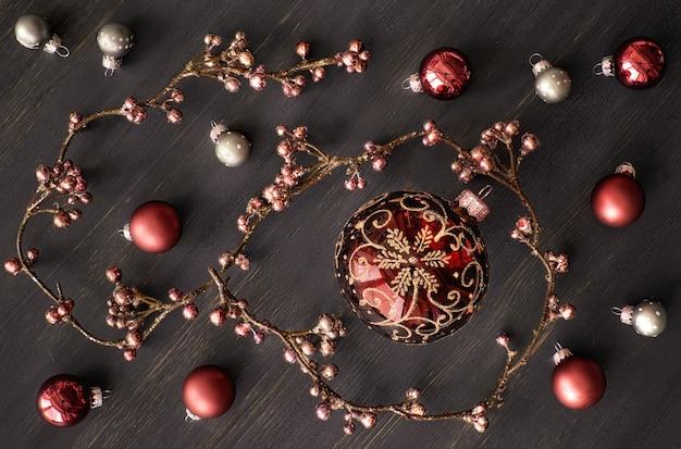 Bożenarodzeniowy tło z błyszczącą kwiecistą girlandą i świątecznymi baubles na zmroku