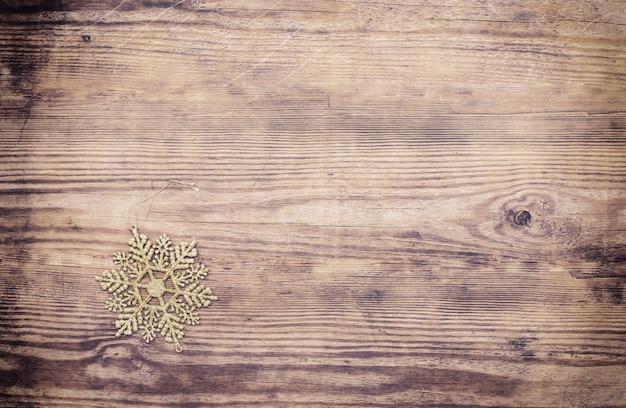 Bożenarodzeniowy tło z boże narodzenie dekoracyjnym złotym płatkiem śniegu