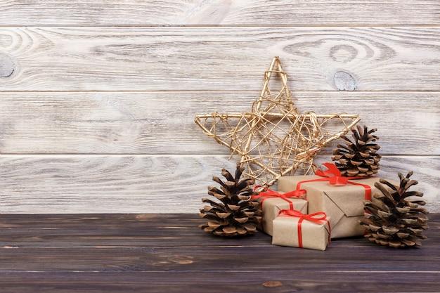 Bożenarodzeniowy tło z bożenarodzeniowym prezentem i gwiazda na drewnianym tle z rożkami. kompozycja na boże narodzenie i szczęśliwego nowego roku