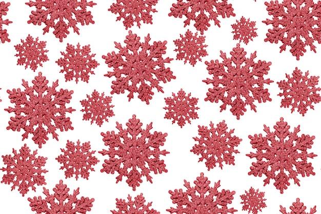 Bożenarodzeniowy tło z czerwonymi płatkami śniegu na białym tle.