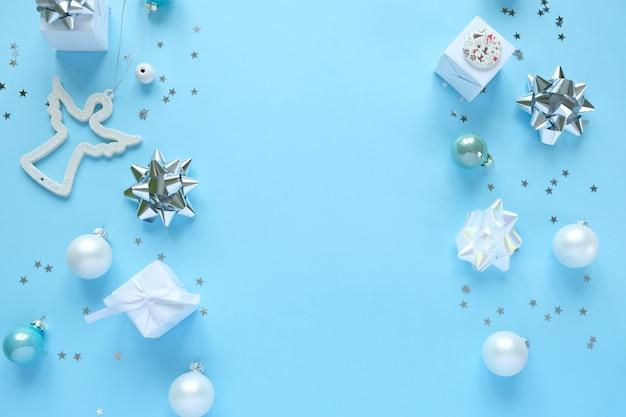 Bożenarodzeniowy tło z dekoracjami i prezentów pudełkami na błękicie