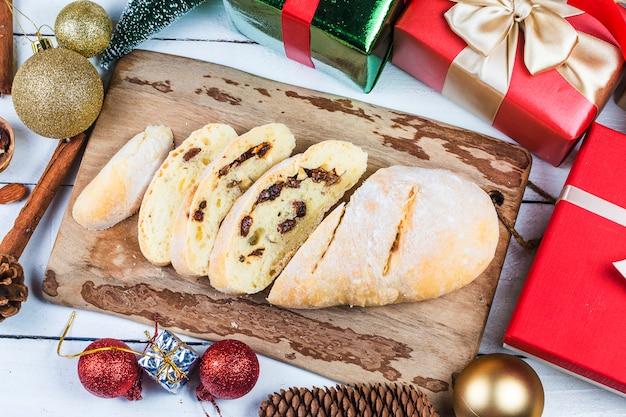 Bożenarodzeniowy tło z dekoracjami i prezentów pudełkami na drewnianej desce, chleb