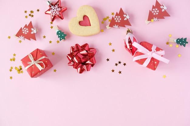 Bożenarodzeniowy tło z dekoracjami i prezentów pudełkami na różowym