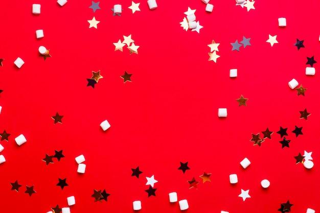 Bożenarodzeniowy tło z gwiazdami i marshmallows na czerwieni.