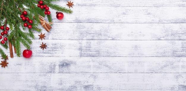 Bożenarodzeniowy tło z jedlinowym drzewem i czerwonymi dekoracjami na drewnianym stole. baner poziomy