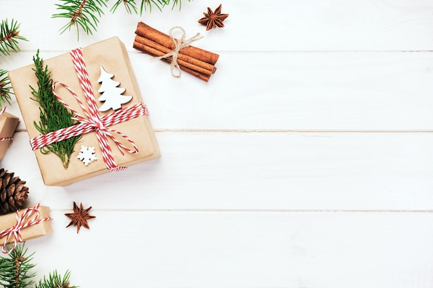 Bożenarodzeniowy tło z jedlinowym drzewem i prezenta pudełkiem na drewnianym stole. widok z góry z copyspace dla swojego projektu
