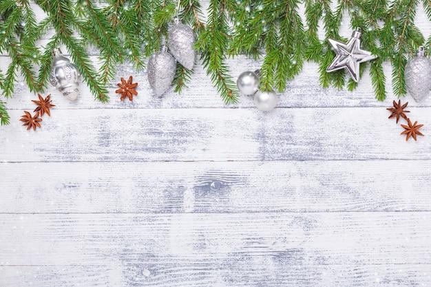 Bożenarodzeniowy tło z jedlinowym drzewem i srebro dekoracjami na drewnianym stole. efekty śniegowe