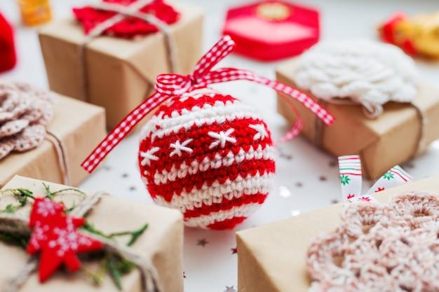Bożenarodzeniowy tło z prezentami, dekoracjami i szydełkowaną ręcznie dekoracyjną piłką.