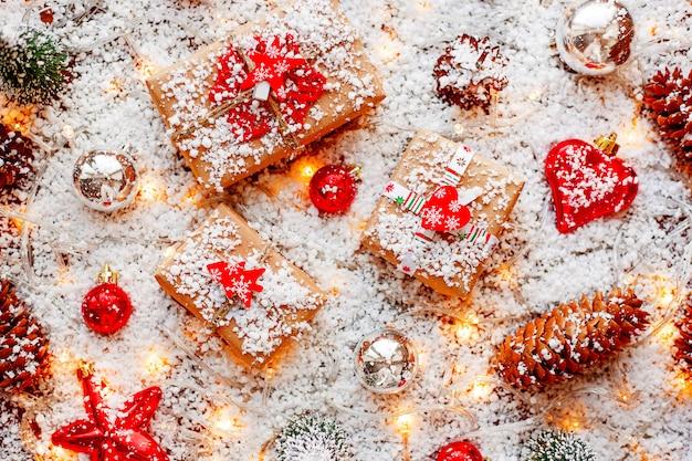 Bożenarodzeniowy tło z prezentami, faborkami, piłkami i różnymi dekoracjami w śniegu z żarówkami.