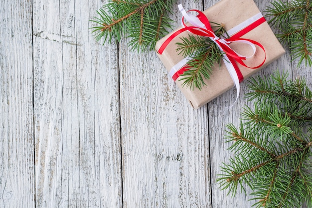 Bożenarodzeniowy tło z prezentem i jodły na białym drewnianym stole,,