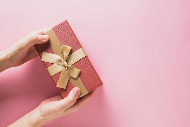 Bożenarodzeniowy tło z rękami trzyma teraźniejszego pudełko