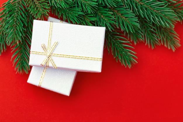 Bożenarodzeniowy tło z srebnymi prezentów pudełkami i zielonymi choinek gałąź na czerwieni papierowym tle. zimowe wakacje koncepcja. minimalna kompozycja.