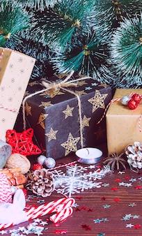 Bożenarodzeniowy wakacyjny prezenta pudełko na dekorującym świątecznym stole z sosnowymi rożkami jedlinowymi gałąź cukierek trzciny dokrętki